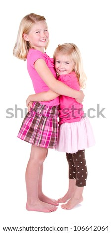 Sisters hugging full length on a white background