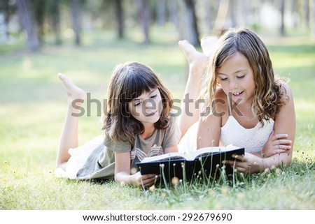 Sisters in the park reading a book - stock photo