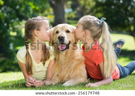 Sisters kissing their dog in the park on a sunny day