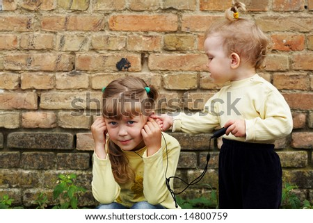 Sisters listens to music on a background of a brick wall