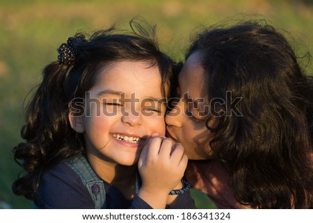 sisters love,close up of little girl kissing her younger sister - stock photo