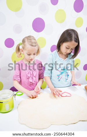 sisters make, delicious cake in kitchen - stock photo