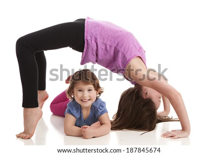Sisters.  Older sister performing a back bend with the younger sister smiling underneath.  Isolated on white. - stock photo