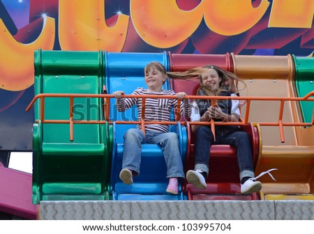 Sisters on carousel in summer carnival - stock photo