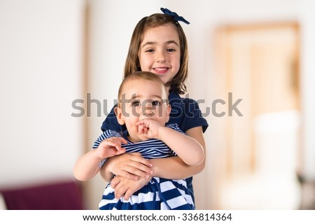 Sisters on chair on unfocused background