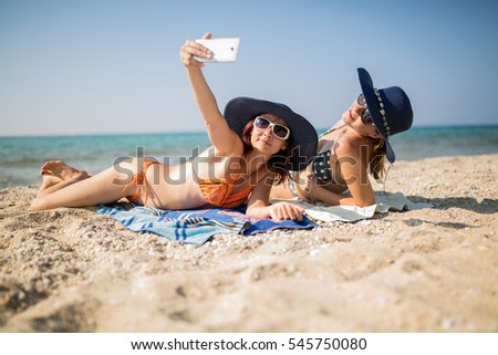 Sisters on the beach taking a self ie