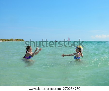 Sisters playing ball in the green beautiful ocean, blue sky in the background, Florida