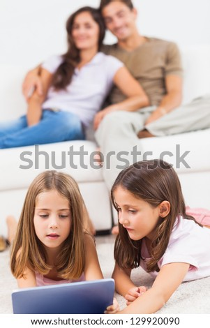 Sisters playing with a tablet in the living room