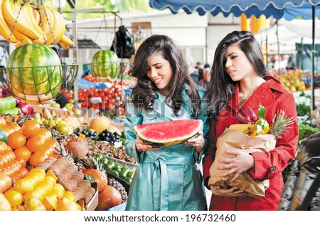 sisters shopping fruits at an outdoors farmers market - stock photo