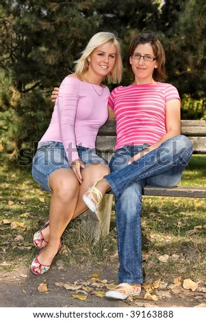sisters sitting on a bench - stock photo