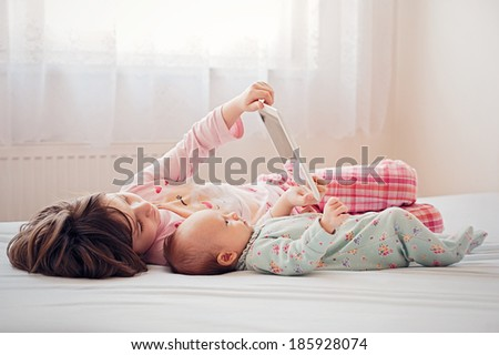 Sisters together lying and watching tablet