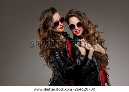 Sisters twins in hipster sun glasses laughing Two fashion models Women smiling positive Friends group having fun, talking Youthful friendship youth adults people culture concept Young girls rock party - stock photo