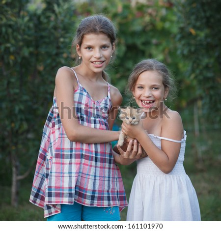 sisters with a kitten - stock photo