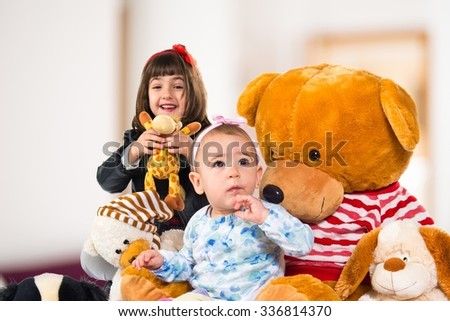 Sisters with many teddies on unfocused background