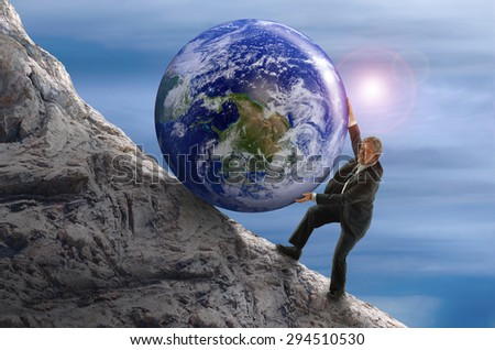 Sisyphus metaphor man struggling to roll a giant Earth rock ball up hill representing business struggles, hard work, environmental threat risk, determination and more. Some elements provided by Nasa. - stock photo