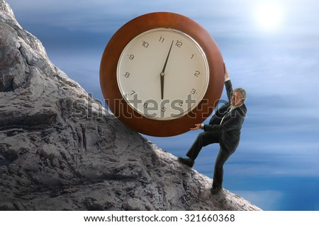 Sisyphys metaphor showing a man struggling to roll a giant clock up a hill representing deadlines, time schedule stress, business struggles, hard work, environmental threat risk and more. - stock photo