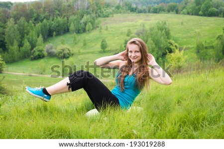 Sit-ups - fitness girl training sit up outside in grass in summer. Happy fit woman doing side crunches with elevated legs while smiling happy. - stock photo