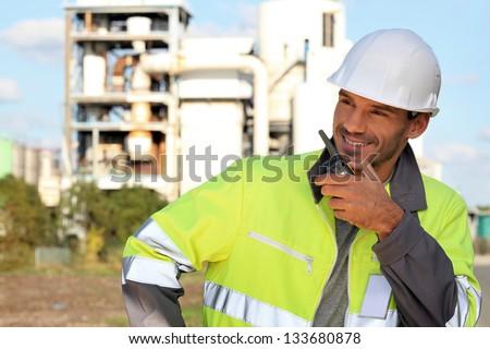 Site foreman communicating via radio receiver - stock photo
