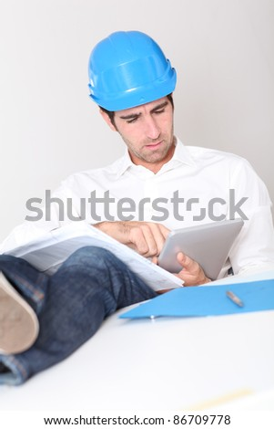 Site manager in office using electronic tablet - stock photo
