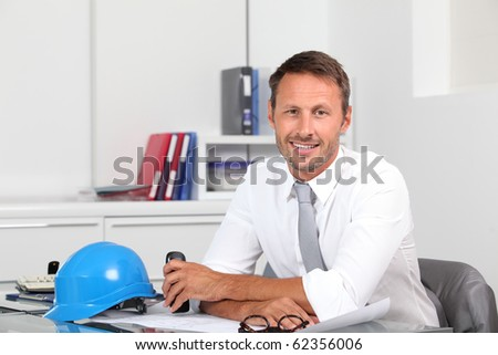 Site manager in the office with blue helmet