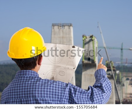 site manager with building plans and background