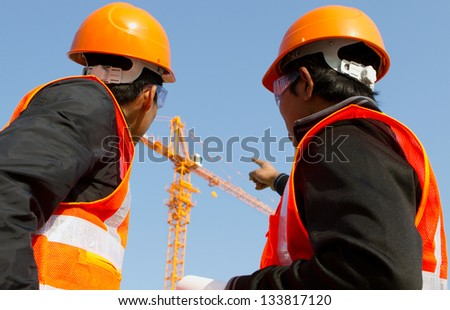 Site manager with safety vest discussion under construction - stock photo