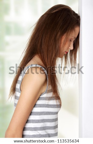 Site view of a young female teen being depressed, resting her head on a wall - stock photo