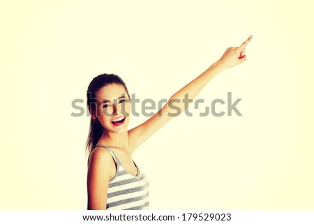 Site view portrait of a beautiful young female caucasian teen pointing up with her finger and smiling to the camera, on white.
