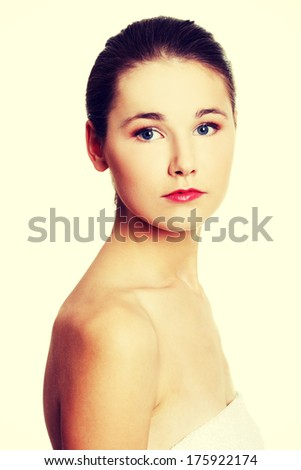 Site view portrait of a young beautiful female caucasian teen being wrapped with a towel, looking to the camera - stock photo