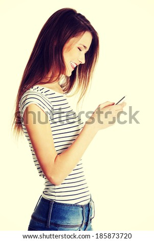 Site view portrait of a young smiling caucasian tenn sending an sms - stock photo