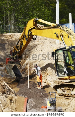 site worker and driver with large bulldozer, digger in action, road-works and construction industry, close-ups view. - stock photo