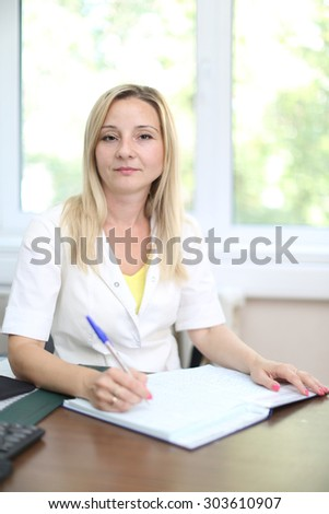 Siting senior nurse writing something on clipboard with pen and looking at camera