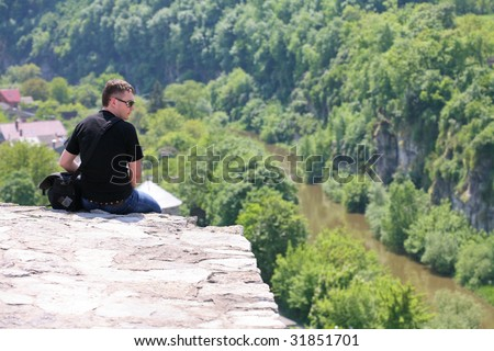 Sitting alone at the top of the precipice - stock photo