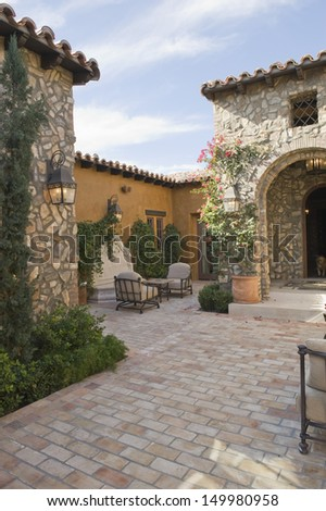 Sitting area in paved courtyard along houses - stock photo