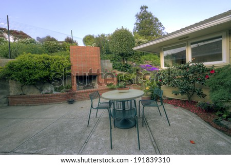 Sitting area / patio with chairs and table surrounded by fire pit. - stock photo