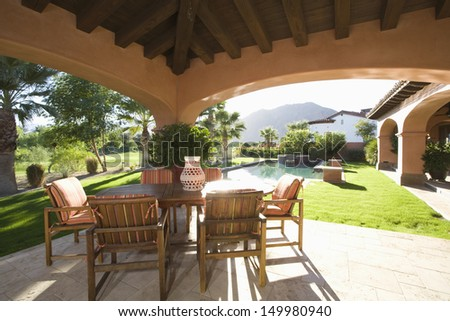 Sitting area with sunlit lawn against mountain - stock photo
