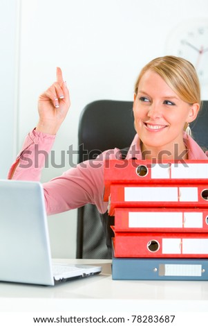 Sitting at office desk with pile of folders smiling modern business woman showing idea gesture - stock photo