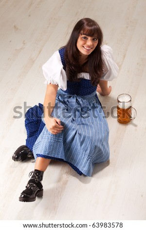 sitting bavarian girl in a costume with a beer mug