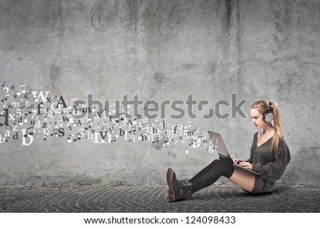 Sitting blonde girl using a laptop computer from which coming out many images and listening to the music with a pair of headphones