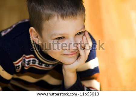 Sitting boy with smiley face on light background