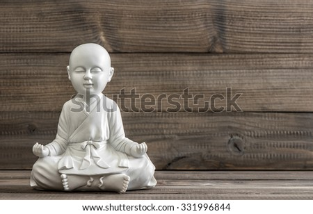 Sitting buddha. White statue on wooden background. Relaxing concept - stock photo