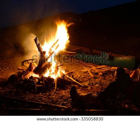 Sitting by a campfire on a beach with a kayak while camping - stock photo