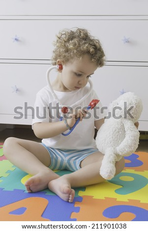 sitting child playing to be a doctor with a toy stethoscope and a teddy bear - stock photo