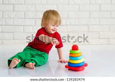 Sitting cute baby boy playing with pyramid from colorful blocks - stock photo