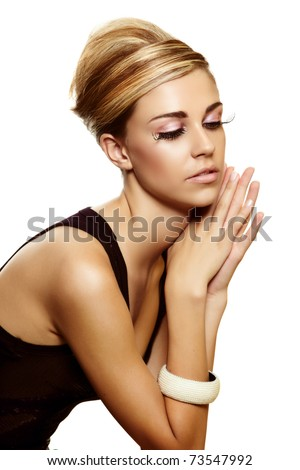 sitting elegant beautiful young woman with blond hair and long false lashes wearing little black dress  . - stock photo