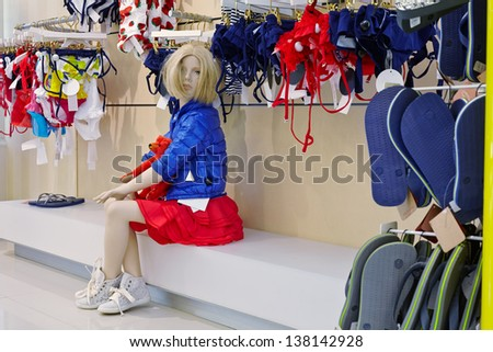 Sitting female fashion doll in clothing store - stock photo
