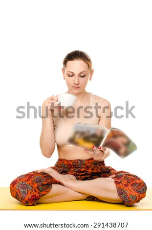 sitting female yogi drinking from cup and reading magazine isolated on white background