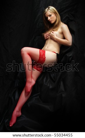 Sitting flirty girl with long slim legs in red nylons. Vintage style low key photography. - stock photo