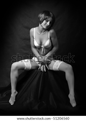 Sitting flirty girl with long slim legs in white nylons. Monochrome low key photography. Great for calendar - stock photo