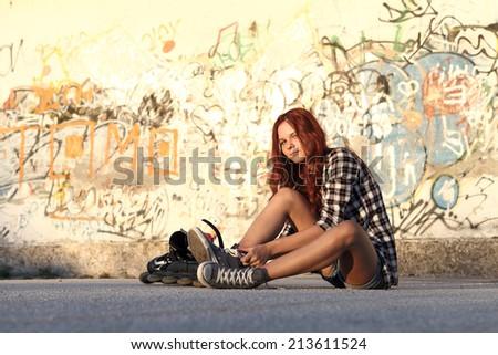 sitting girl with roller skates on graffiti background - stock photo